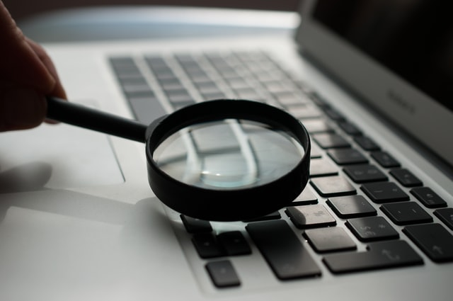 Hand holding a magnifying glass over a computer keyboard