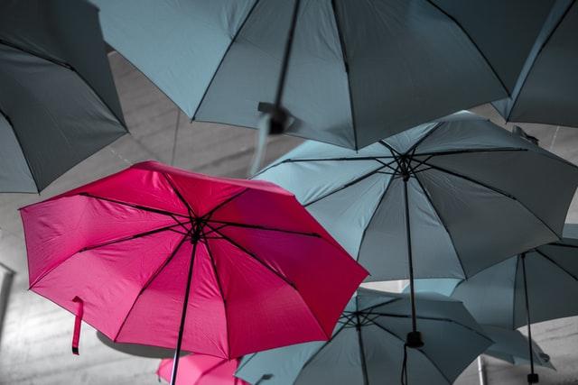 Red umbrella among gray umbrellas