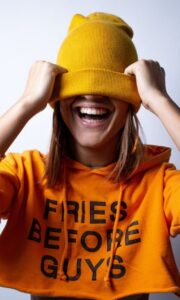 Girl wearing a shirt that reads fries before guys
