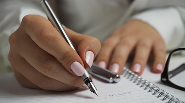Home Business Woman Writing in Notebook