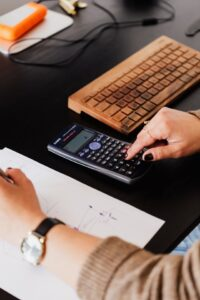 Woman Working with Paper and a Calculator on Desk