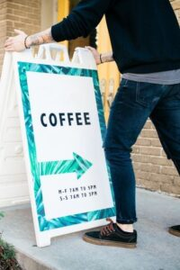 Man Positioning a Free Ad Sign Outside a Coffee Shop