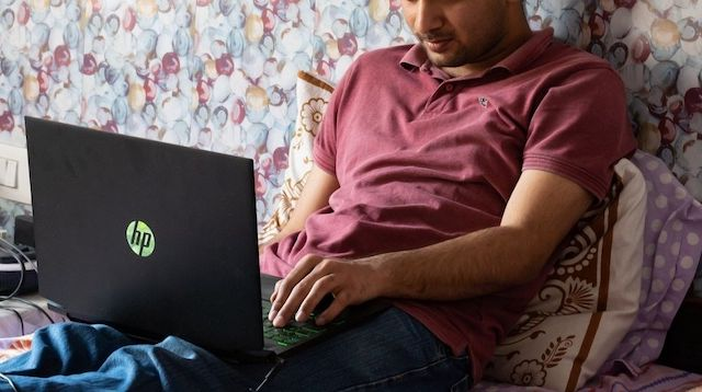 Man Working Remotely on a Laptop in Bed