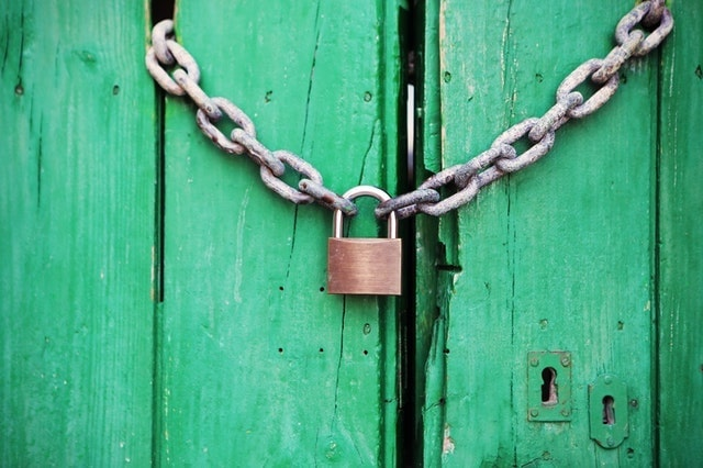 Padlock over green barn door
