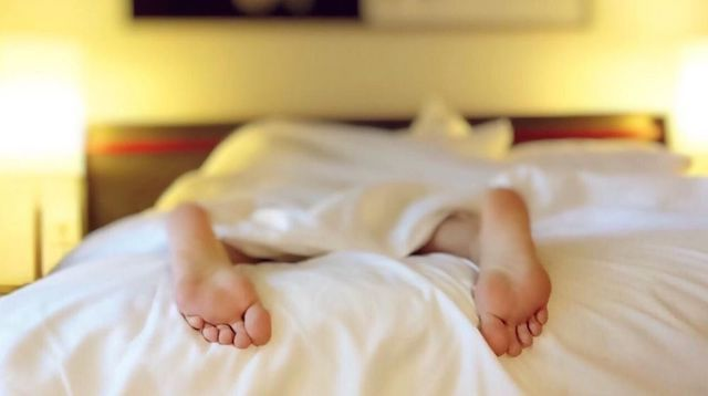 Person Lying in Bed with Only Their Feet Showing