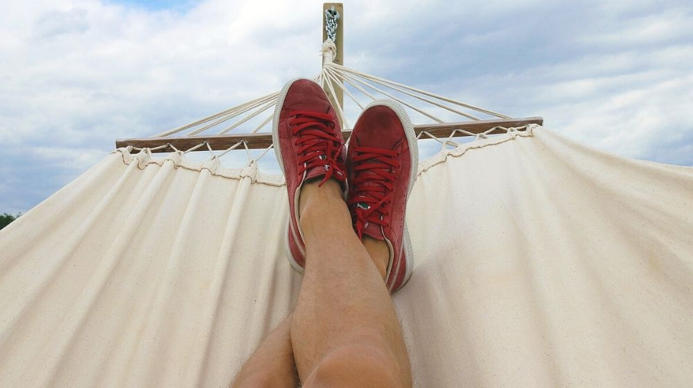 Person on Hammock Wearing Red and White Sneakers