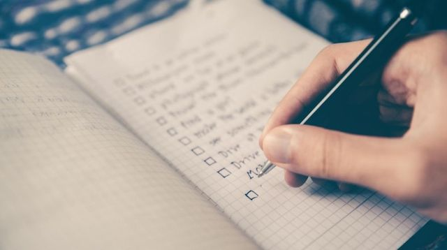 Person Writing a List of Tasks on Paper