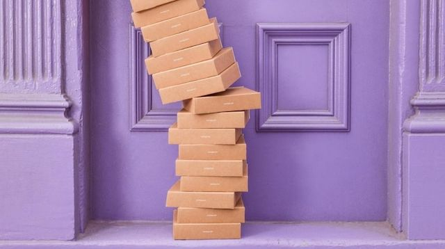 Tall Stack of Boxes Piled Up Outside Purple Door