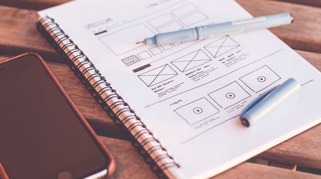 Web Design Company Notebook Beside an iPhone