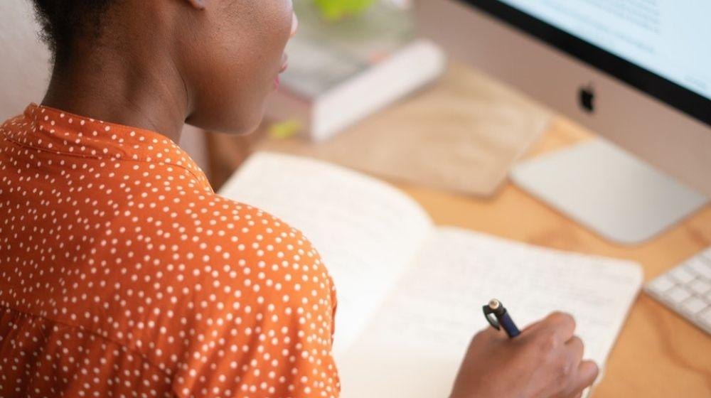 Woman in orange shirt working at desk.