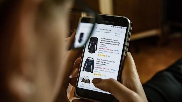 Woman Looking at Winter Coats on Her Phone