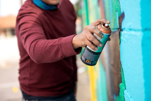 Person with can of spray paint spraying a wall