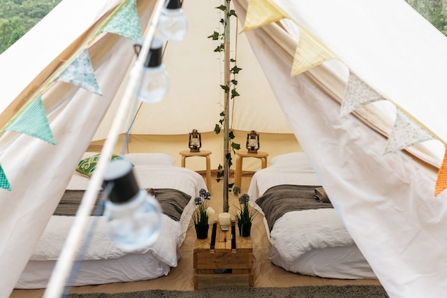 Glamping tent with beds, table lamps and potted plants