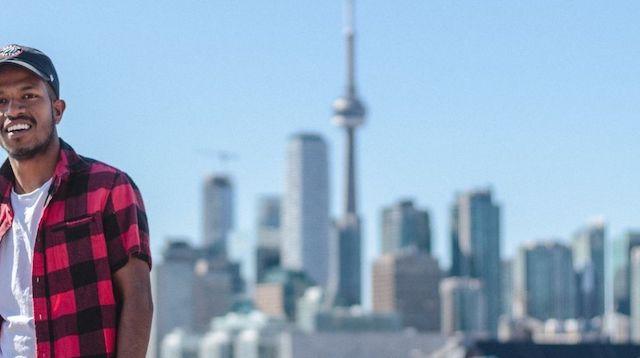 Man posing against a Toronto skyline
