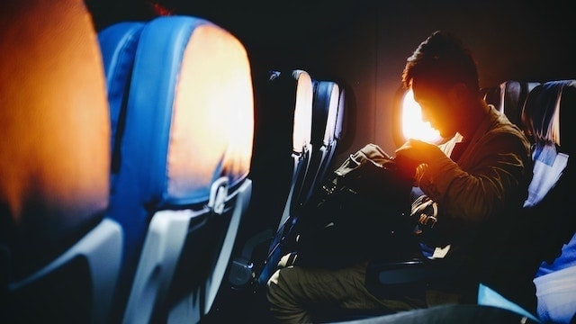 Man seated on airplane with a backpack