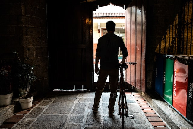 Man standing near an entryway with a bike