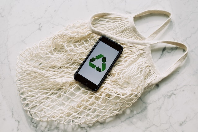Netted shopping bag with smartphone showing recycle symbol