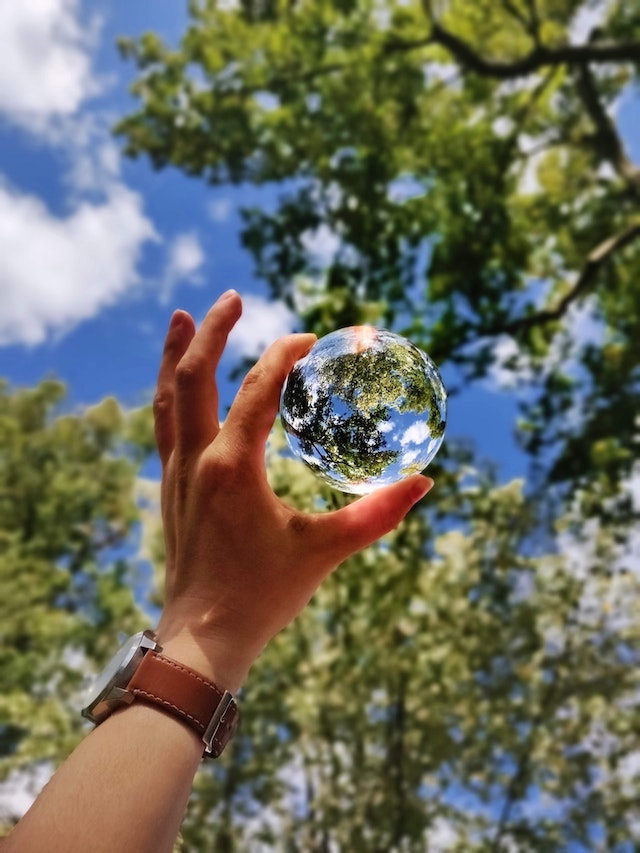 Person holding a clear glass globe to the sky