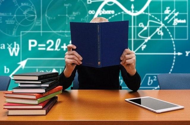 Teacher sitting at a desk in front of a blackboard