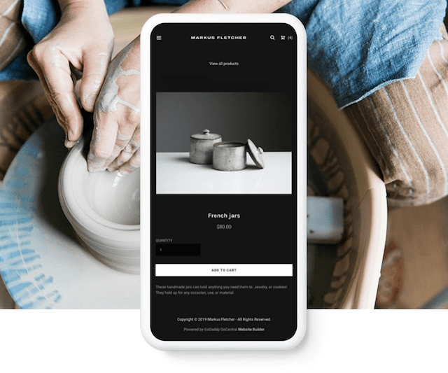 website-on-a-smartphone-overtop-a-pic-of-a-potter-at-work