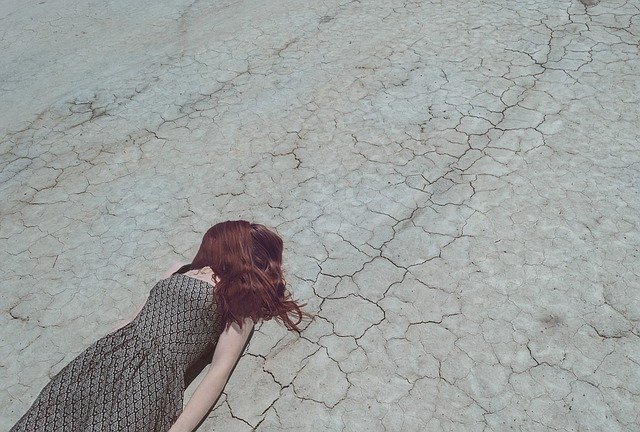 Woman lying on dry and cracked earth