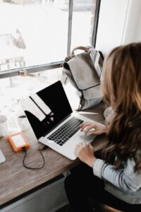 Woman sitting at a desk typing on a laptop