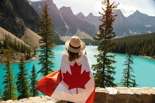 Woman wrapped in Canadian flag enjoying scenic view